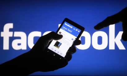 A user uses Facebook in front of the Facebook sign